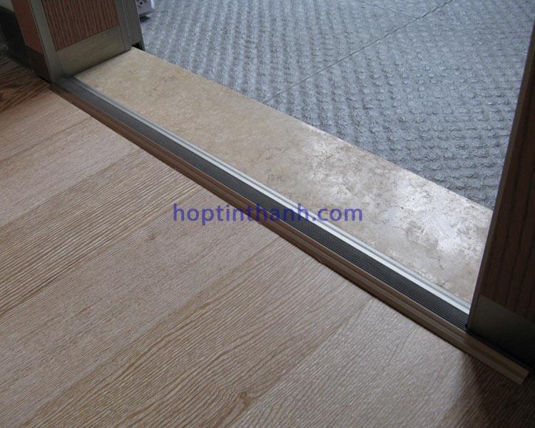 Dùng nẹp mặt bằng thông phòng NCP8.0 trang trí khe nối giữa sàn gỗ và đá ở cửa phòng